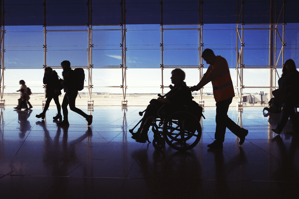 Photograph of a disabled passenger travelling through the airport, while using a wheelchair.